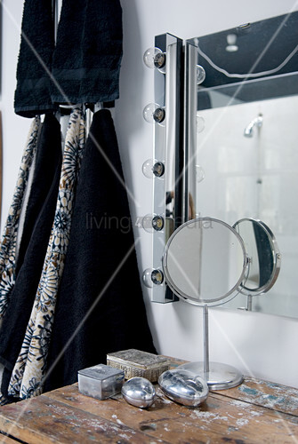 Modern bathroom mirror with row of lights on one side, small silver boxes on old table and black towels hanging on wall