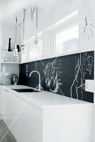 White designer kitchen with black splashback behind sink worksurface