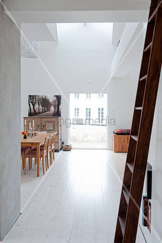 Wooden ladder in front of doorway showing view of minimalist interior with dining area next to floor-to-ceiling window