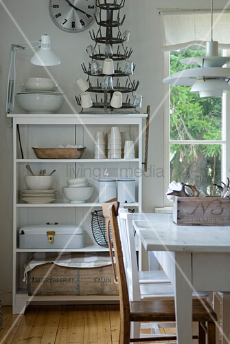 Dining area with classic pendant lamp and crocker on white-painted shelves in corner of room