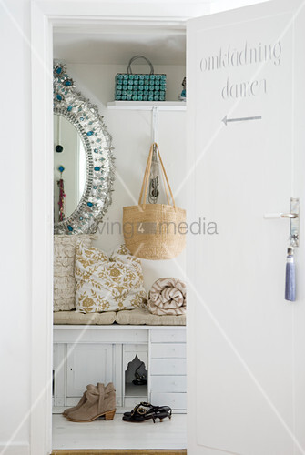 Open door with view into feminine dressing area with glittery mirror and integrated bench