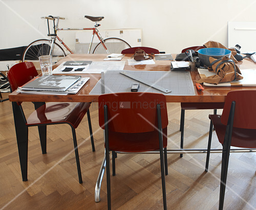 Work utensils on table and Bauhaus-style chairs in front of bicycle leaning on wall