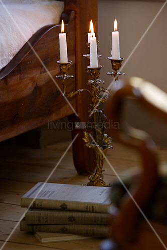 Lit candles in four-armed candlestick on floor next to bed in country-style bedroom