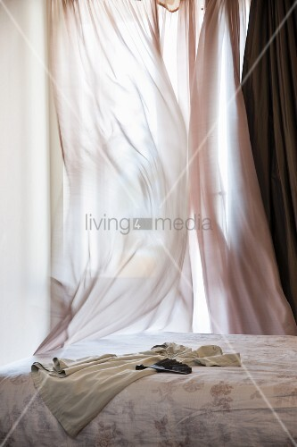Bed in front of window veiled in fluttering, airy curtains