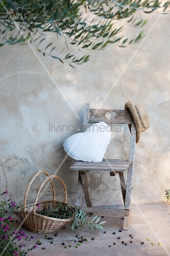 Wooden chair with heart-shaped cushion below olive tree