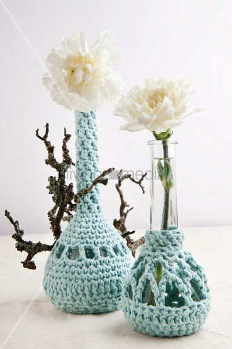 Umhäkelte Blumenvasen mit jeweils einer weissen Nelke