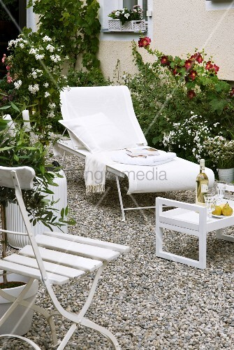 White sun lounger, folding chair and tray table on gravel surface in garden