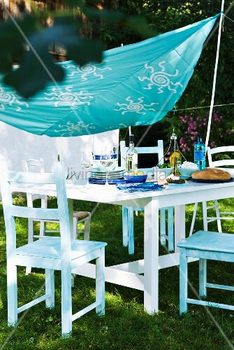Cloth painted with stencilled pattern as awning above set table in garden