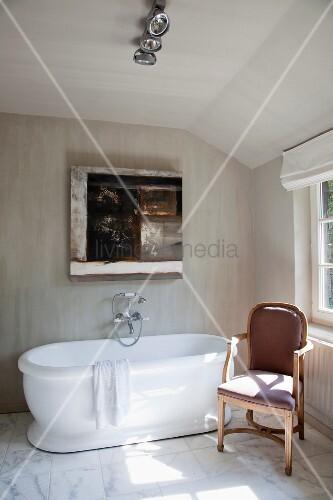 Badezimmer Mit Dachschräge Und Geädertem Marmorboden; Modernes Gemälde über  Der Freistehenden Wanne Und Antiker Polsterstuhl Als Ablage