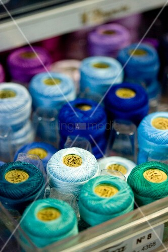 Spools of thread in various shades of blue in storage box