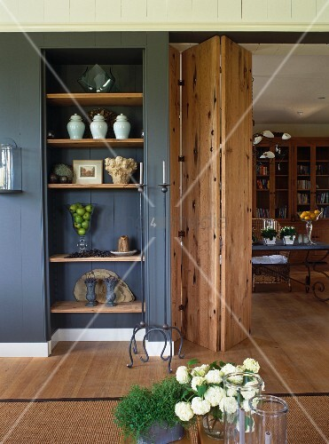 holzverkleidete wand mit nische und eingebautem regal neben durchgang mit holzfaltt r bild. Black Bedroom Furniture Sets. Home Design Ideas