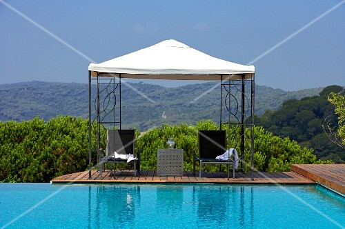 Chairs and table under pergola next to infinity pool with view of mountain landscape
