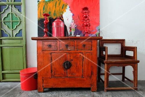 alte asiatische kommode mit deko objekten vor modernem bild neben holzstuhl in schlichtem zimmer. Black Bedroom Furniture Sets. Home Design Ideas