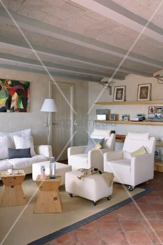 Helle Polstermöbel Auf Rollen Und Holzhocker Als Beistelltische In  Mediterranem Wohnzimmer Mit Rippendecke Und Terracottafliesen