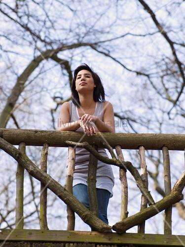 Dark-haired woman standing on wooden bridge
