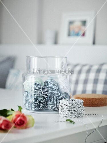 Various rolls of ribbons in a glass container on a table with a roll of black-and-white twine in the foreground