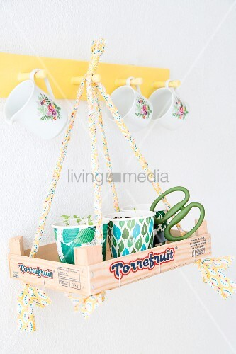 Seedlings in paper cups in recycled wooden crate hung from yellow coat rack by ribbons