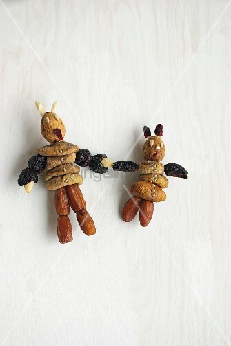 Figurines made from dried dates and figs on white surface