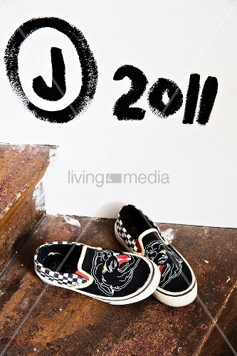 Shoes on rustic wooden step below black letters and digits painted on white wall