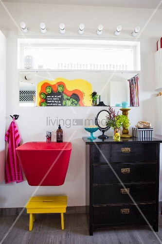Red sink and black chest of drawers below mirror on wall