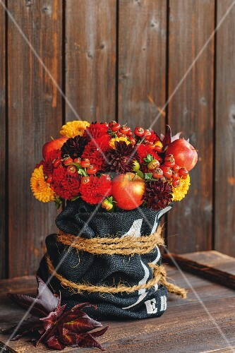Autumnal flower arrangement in shades of red with dahlias, rose hips and apples
