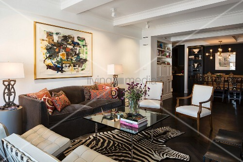 Zebra-skin rug in eclectic lounge area with dining area in background