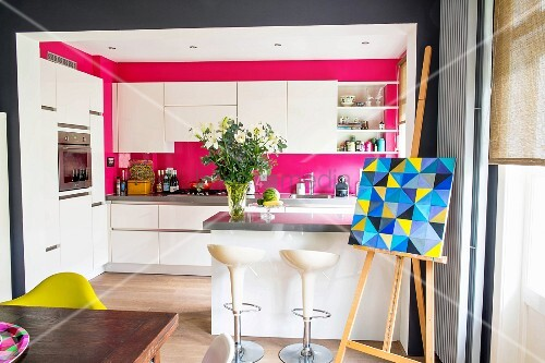 Open-plan kitchen with white, modern furnishings and hot pink walls