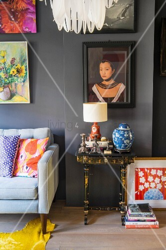 Side table in living room below artworks on grey wall