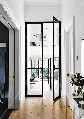 Flur mit offener, schwarzer Glasflügeltür und Durchblick auf Wohnbereich und Galerie