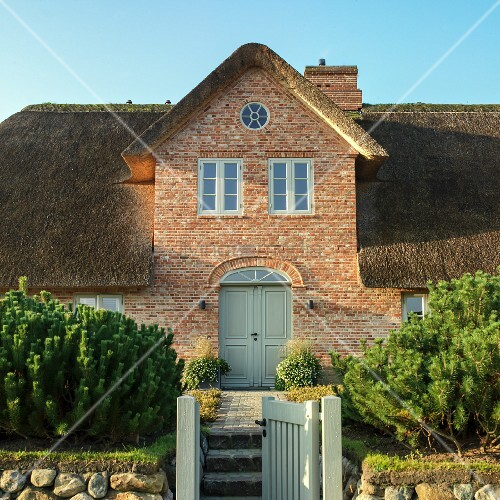 Nordic brick house with thatched roof under blue sky