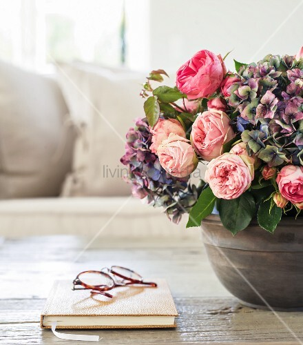 Bouquet of roses and hydrangeas next to spectacles on book