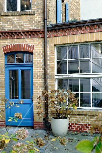 Brick façade with blue door and industrial-style windows