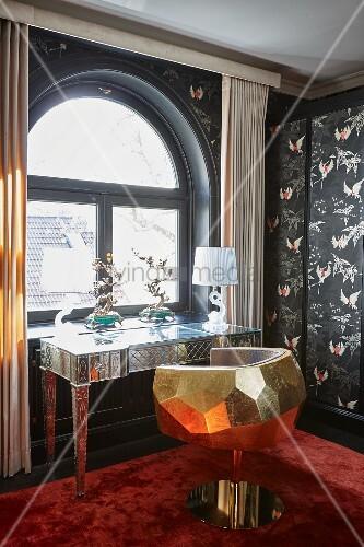 Kunsthandwerklicher Schreibtisch und goldfarbener Schreibtischsessel vor Rundbogenfenster in edlem Ambiente