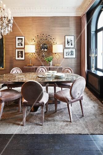 Elegantes Esszimmer mit Polsterstühlen, ovalem Esstisch und gerahmten Fotos neben Wandspiegel in Stahlenform