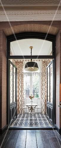 Versilberbert Bistrotisch mit zwei Stühlen vor Fenstertür
