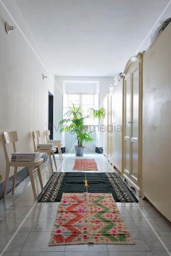 Verschiedenen Teppichläufer auf Marmorfliesenboden, Stühle und Schränke auf breitem Gang