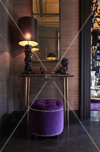 Violetter, eleganter Sitzpouf vor Wandtisch mit kunsthandwerklicher Tischleuchte und Tierfiguren