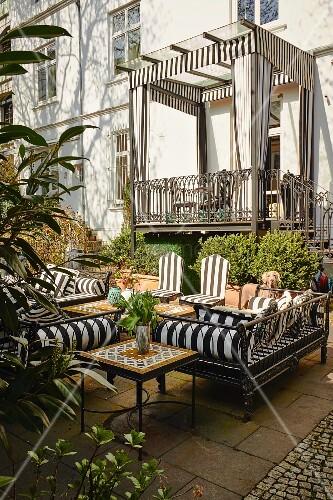 Terrasse mit Outdoormöbeln und überdachter Balkon mit Schabracken und Vorhängen