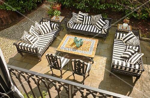 Blick auf Terrassenplatz mit schwarz-weiss gestreiften Polstern auf Outdoormöbeln