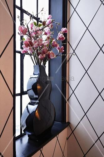 Rosafarbene Blütenzweige in schwarzer Vase vor Sprossenfenster