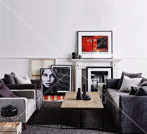 Sofagarnitur in Grautönen und Couchtisch mit rustikaler Tischplatte, weiße Kaminverkleidung und gerahmte Fotokunst