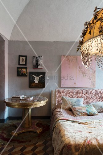 Antique table next to bed and pictures on wall of bedroom with vaulted ceiling