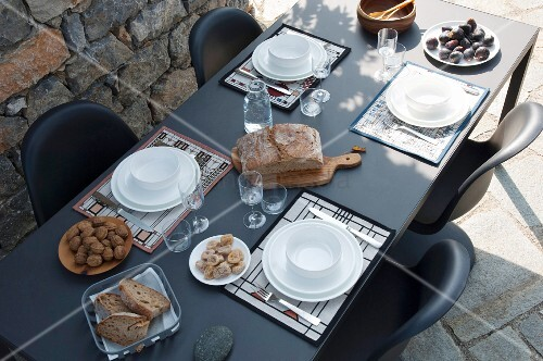 View down onto black table set with white crockery on terrace
