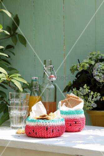 Gehäkelte Melonen-Körbchen mit Keksen neben Gläsern und Bügelflaschen auf Gartentisch