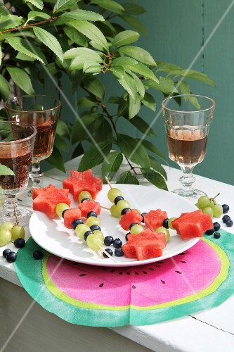 Fruit skewers on white plate and hand-made place mat