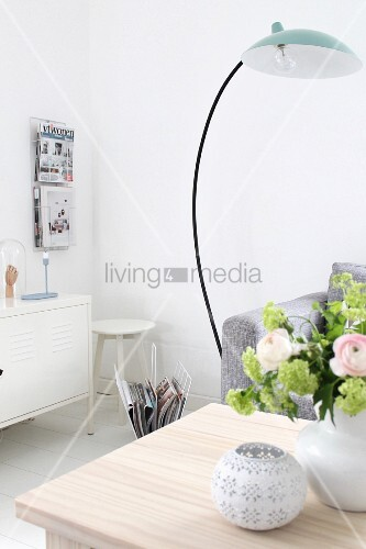 Arc lamp, flowers on coffee table, white metal sideboard and magazine rack