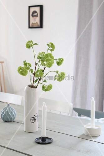 zarte gr ne bl tenzweige in weisser vase auf holztisch mit kerzen bild kaufen living4media. Black Bedroom Furniture Sets. Home Design Ideas