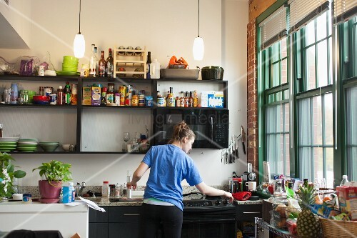 Young woman stood at kitchen counter cooking
