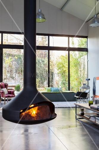 Offener Wohnbereich mit Hängekamin und Kaminfeuer in Loftwohnung