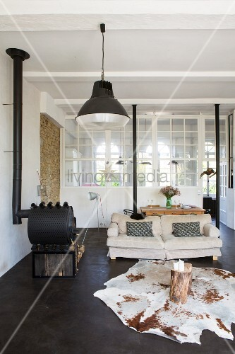 Animal-skin rug, tree stump tables and wood-burning stove in lounge area with interior windows